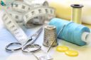 sewing accessories with blue and yellow threads, tape measure and scissors on fabric background