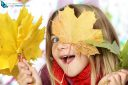 girl hiding behind autumn leaves looking at the camera