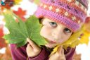 Autumnal mood of a little girl in yellow autumn leaves looking at camera