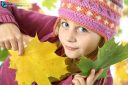 Portrait of young girl in autumn with multicolored leaves, looking at the camera