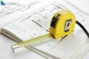 Yellow measuring tape on a construction plan