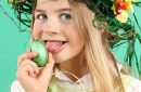 Young girl wearing fun hairstyle on Easter day eats chocolate eggs