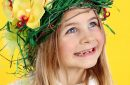 Smiling Happy Young Girl Wearing Headdress of Spring Flowers, Easter Eggs and Feathers.
