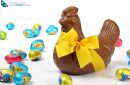 Chocolate hen with yellow ribbon and colorful Easter eggs, isolated on white background