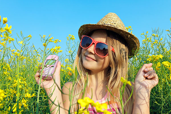 enfant avec téléphone dans un champ