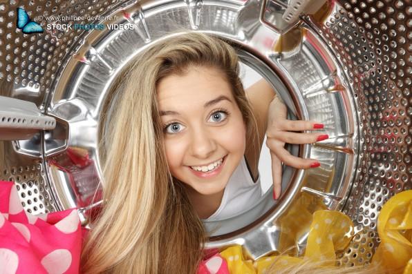 Portrait en gros plan d'une jeune femme blonde de 18 ans vue de l'intérieur d'un tambour de machine à laver