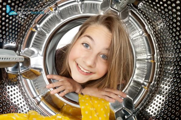 Portrait jeune enfant regardant à l'intérieur d'une machine à laver le linge
