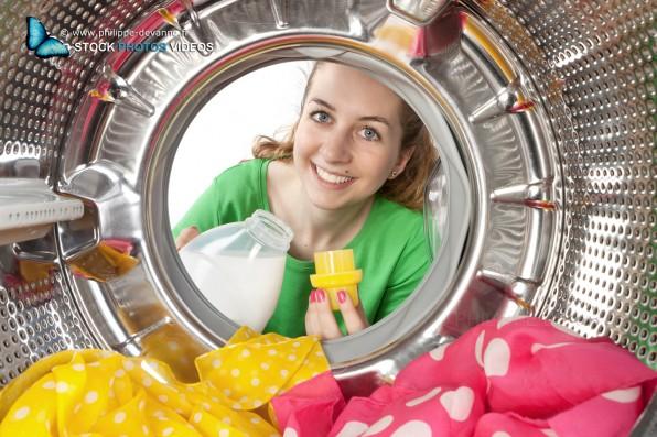Jeune femme charge du linge de couleur dans une machine à laver. vue de l'intérieur du tambour