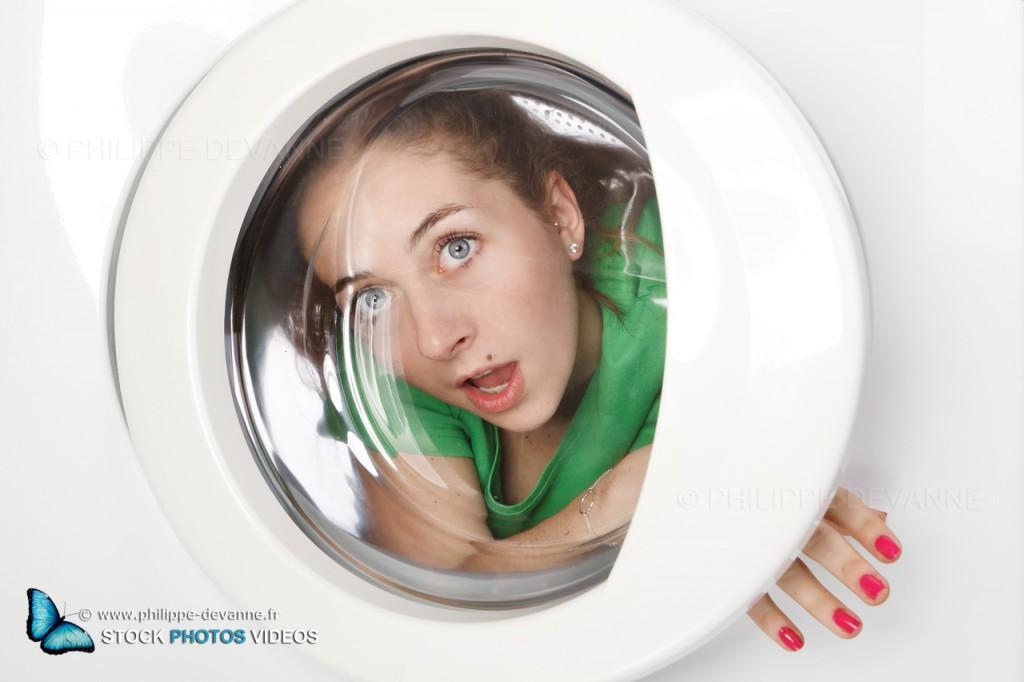 photo fun et comique d'une jeune femme  à l'intérieur d'une machine à laver. vue de l'extérieur du hublot