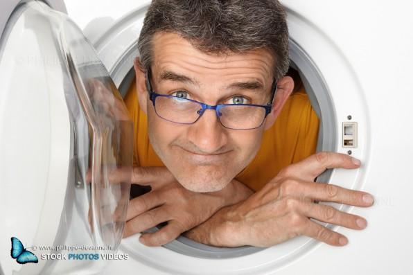photo fun et comique d'un homme de 45, 50 ans à l'intérieur d'une machine à laver le linge, vue de l'exterieur coté hublot