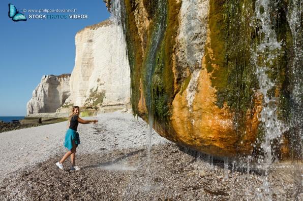 Enfant jouant avec une cascade au bord de la Falaise d'Étretat sur le littoral de la Manche en pay de Caux , département de seine-Maritime, région Haute-Normandie, France