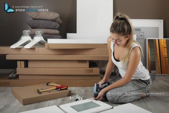 jeune fille blonde monte un meuble en kit