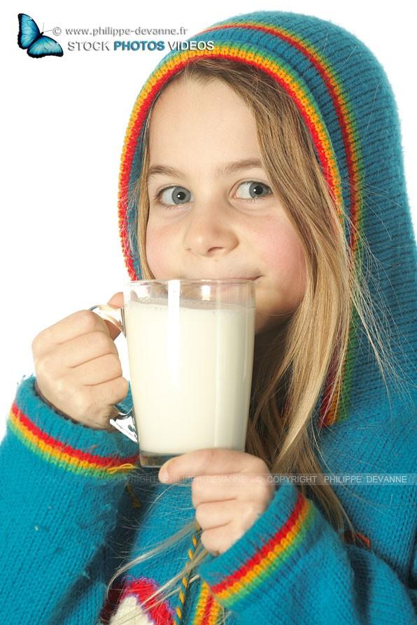 Jeune fille souriante boit du lait avec grand plaisir