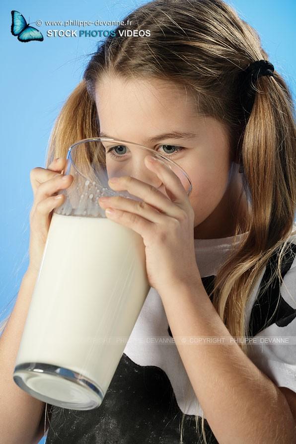 Enfant avec des couettes et un t-shirt couleur vache boit un enorme verre de lait