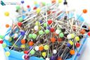 Blue box of multicolored sewing pins on a white background