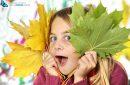 Pretty little girl holding autumn leaves on white background