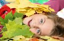 Close-up of a pretty girl lying in a pile of multicolored autumn leaves
