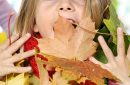 girl looking at camera and playing with a bunch of autumn leaves