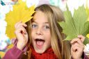 Pretty little girl holding autumn leaves and looking at the camera.