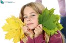 girl holding autumn leaves on white background