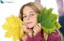 girl holding autumn leaves on white background