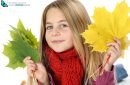 Young girl portrait with autumn leaves in studio