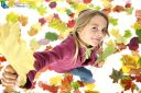 Little girl playing with autumn leaves on white background
