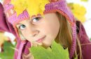 Portrait of little girl in autumn with multicolored leaves and in woolen cap.
