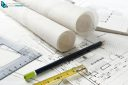 Work tool equipment laid out on house and kitchen construction plans with rolls of architect drawings