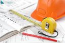 hard hat , measuring tape and pincil on architectural blueprints