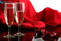 Close up of two glasses of champagne on red background with ribbon