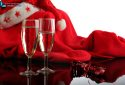 Two glasses of champagne, a ribbon and a red Santa Claus costume