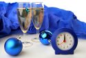 Two glasses of champagne with a clock and Christmas balls for the new year