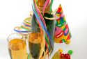 bottle and glass of champagne, paper ribbon, confetti, party hats and gifts on white background.