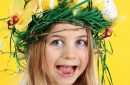 Young happy girl wearing straw headdress made of spring flowers, Easter eggs and feathers on yellow background.