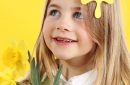Portrait little blonde girl on yellow background with spring daffodil flowers