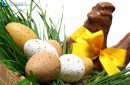Traditional basket of Easter eggs on fresh grass with a chocolate hen