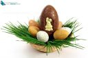 Big chocolate Easter eggs with small ones in a basket with green grass on white