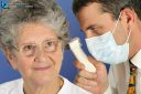 A doctor with a mask looks into the patient's ear with an otoscope. The patient is a woman over 65