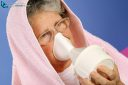 65 year old woman with towel over head inhaling essential oil vapor as alternative therapy