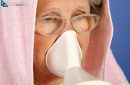 healthcare concept, colds, rhinitis and sore throat. Old gray-haired woman uses inhaler to infuse medicine and heal herself.