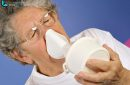 Close-up 65-year-old sick woman using inhaler to treat colds and sore throat