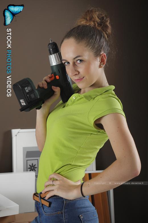 jeune femme fait du bricolage avec une perceuse visseuse