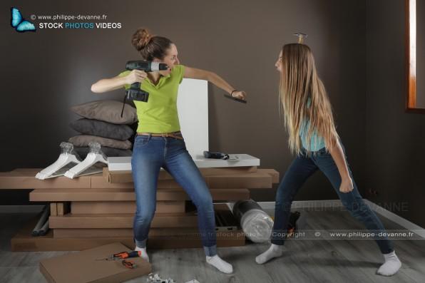 Deux jeunes filles s'affrontent a coup de marteau et perceuse dévisseuse en montant un meuble en kit