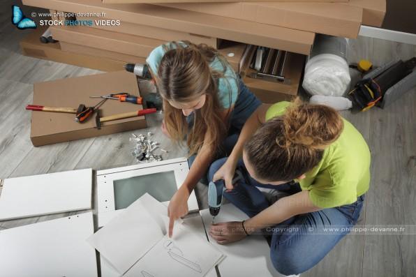 Deux jeunes filles assemblent un meuble de chambre en kit