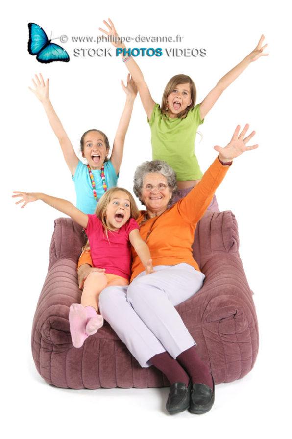Petits enfants avec  leur grand-mère lèvent haut les mains de joie
