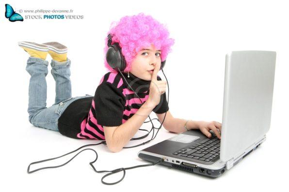 Jeune fille avec cheveux rose écoutant de la musique et écrivant sur un ordinateur portable dit de ne pas parler de la main